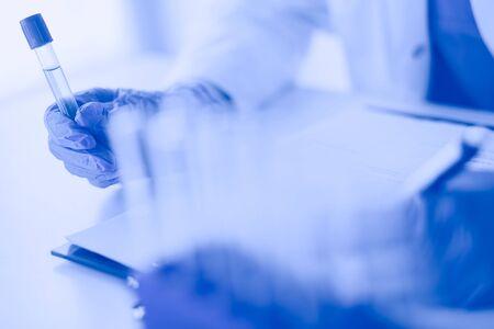 Die Forscherin ist von medizinischen Fläschchen und Flaschen umgeben, die auf weißem Hintergrund isoliert sind