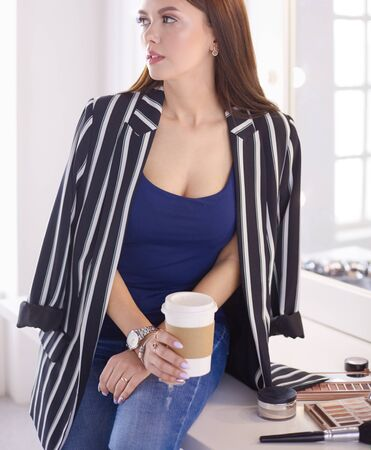 Stylish female make up artist drinking cup of cappuccino and waiting for visitors at modern interior Zdjęcie Seryjne