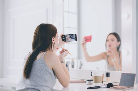 Beauty blogger filming makeup tutorial with smartphone in front of mirror