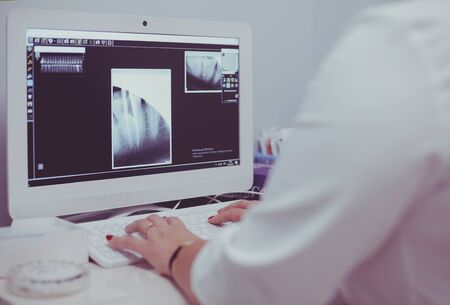 A female medical doctor looking at x-rays and using laptop in a hospital 免版税图像