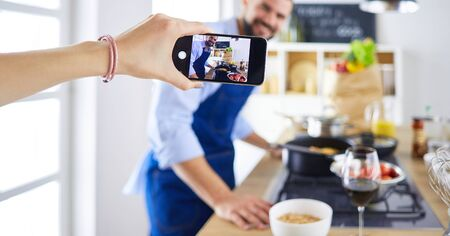 Portrait of handsome man filming cooking show or blog Banque d'images