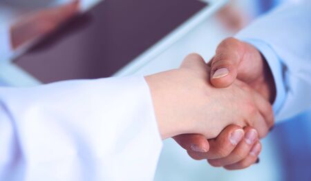 Young medical people handshaking at office .