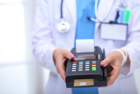 Doctor is holding payment terminal in hands. Paying for health care. Doctor.