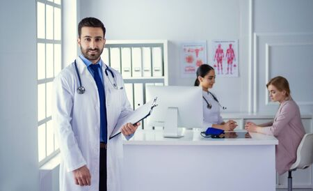 Smiling doctor man standing in front of his team and patient Imagens