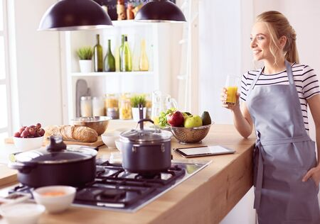 Attractive woman holding a glass of orange juice while standing in the kitchen Foto de archivo