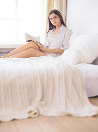 Portrait of woman using tablet and drinking coffee while sitting on the bed in the morning Banco de Imagens