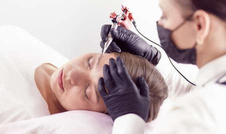 Young woman undergoing procedure of eyebrow permanent makeup in beauty salon