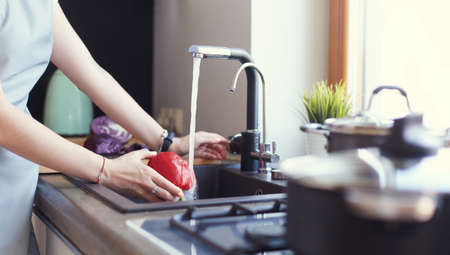 Woman washing vegetables. Beautiful young woman washing vegetables for salad and smiling while standing in the kitchen