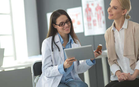 Doctor and patient discussing something while sitting at the table . Medicine and health care concept Foto de archivo