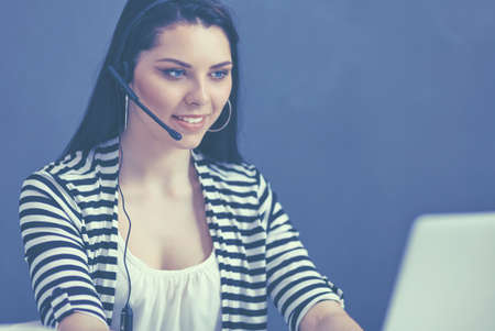 Beautiful business woman working at her desk with headset and laptop Stock Photo