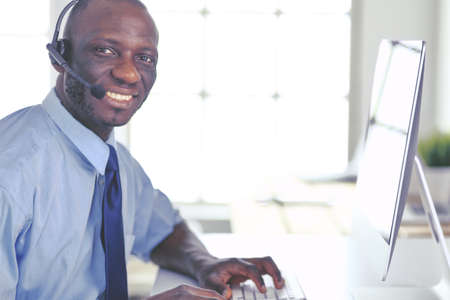 African american businessman on headset working on his laptop Banco de Imagens