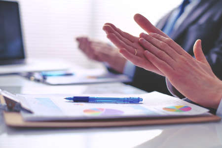 Business people clapping, sitting on the desk
