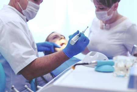 Detail of hand holding dental tools in dental clinic. Dentist Concept