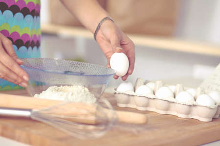 young woman in the kitchen, isolated on background Stock Photo
