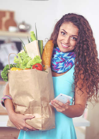 Smiling woman with mobile phone holding shopping bag in kitchen Stock Photo