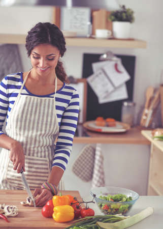 Young woman cutting vegetables in kitchen Stock Photo