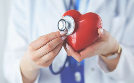 A doctor with stethoscope examining red heart, isolated on white background Stock Photo