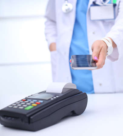 Doctor is holding payment terminal in hands. Paying for health care. Doctor