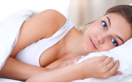 A beautiful young woman lying in bed comfortably and blissfully