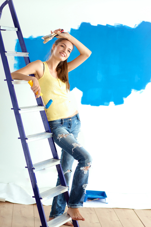 paint wall: Beautiful young woman doing wall painting, standing near ladder Stock Photo