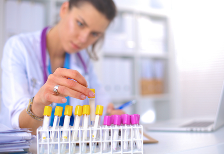 in lab: Investigador de la mujer est� rodeada de viales y frascos de medicina, aislado en blanco Foto de archivo
