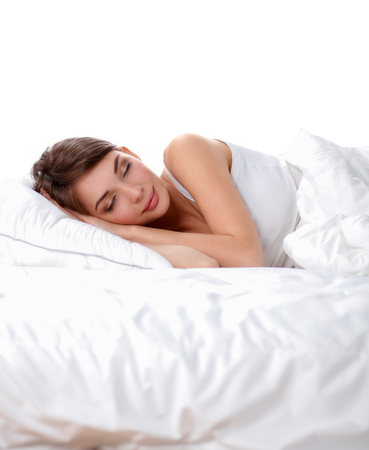 1 woman only: Beautiful girl sleeps in the bedroom, lying on bed. Stock Photo