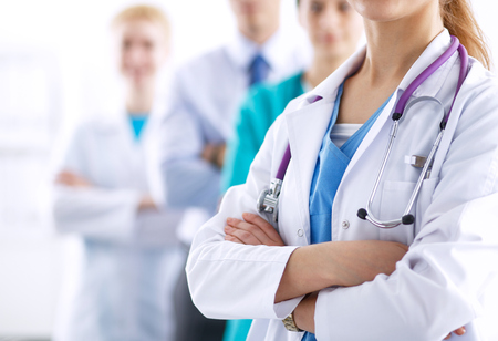 doctor care: Attractive female doctor in front of medical group .