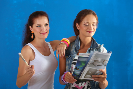 housepainter: Two beautiful young woman doing wall painting . Stock Photo