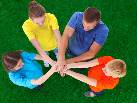 joining: People joining their hands on green grass Stock Photo