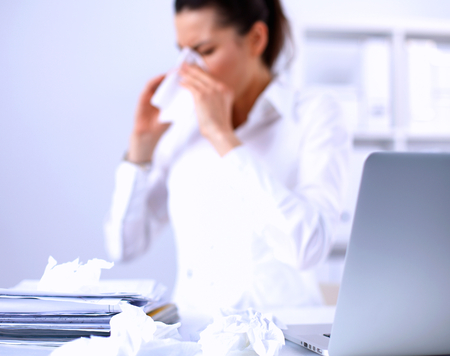 blow: Young businesswoman blowing her nose, sits at her desk .