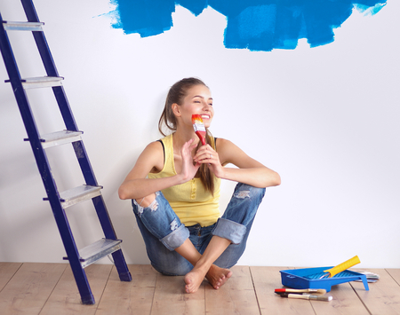 painter girl: Portrait of female painter sitting on floor after painting.