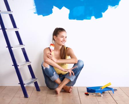 塗装後の床に座って女性画家の肖像画。