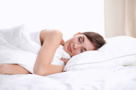 bedding: Beautiful girl sleeps in the bedroom, lying on bed. Stock Photo