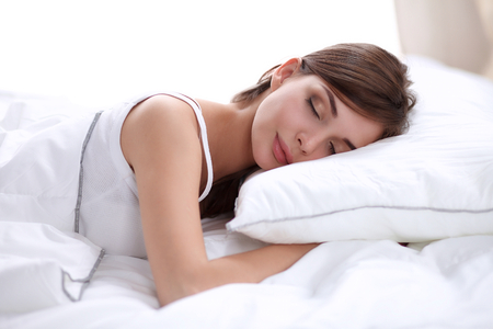 sleeping woman: Beautiful girl sleeps in the bedroom, lying on bed, isolated Stock Photo