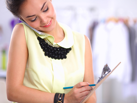 1 young woman only: Pretty fashion designer working in office using mobile phone, isolated