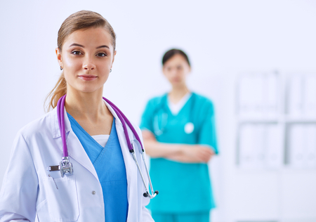 medical doctors: Woman doctor standing with stethoscope at hospital Stock Photo