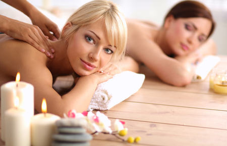 spa treatment: Two young beautiful women relaxing and enjoying at the spa Stock Photo