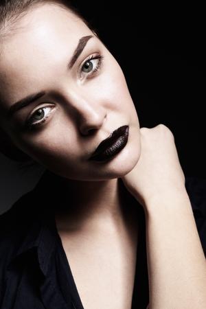 美しい若い女性の顔の肖像画。黒の背景上に分離。