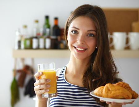 devouring: Young woman with glass of juice and cakes . Stock Photo