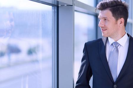 only man: Portrait of businessman standing near window in office .