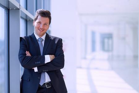 Portrait of businessman standing near window in office .