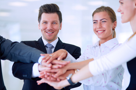 Business people with their hands together in a circle .