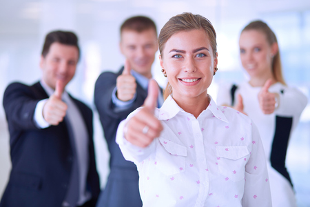 Happy business team showing thumbs up in office .