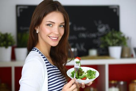 gefesselt: Junge Frau isst Salat und hält einen gemischten Salat.