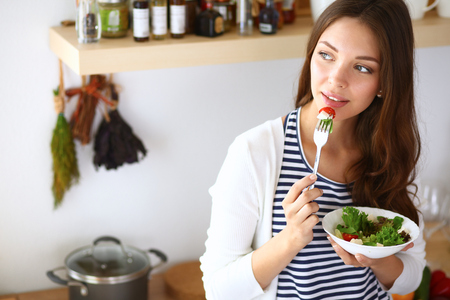 healthy eating: Young woman eating salad and holding a mixed salad . Stock Photo