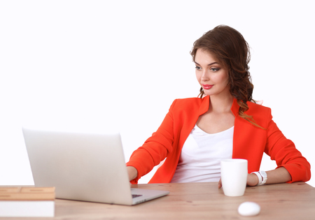 lady in red: Attractive woman sitting at desk in office, working with laptop
