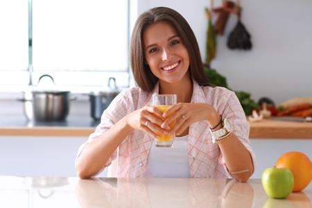 mujer sentada: Joven mujer sentada en una mesa de la cocina.