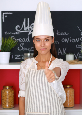 culinary skills: Chef woman portrait with  uniform in the kitchen and showing ok . Stock Photo