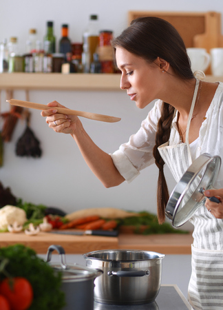 people cooking: Cooking woman in kitchen with wooden spoon.