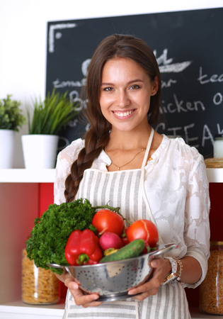 wife: Smiling young woman holding vegetables standing in kitchen .